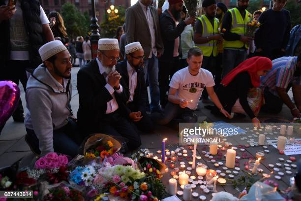 TOPSHOT People pray and light candles set up in front of floral tributes in Albert Square in Manchester northwest England on May 23 in solidarity...
