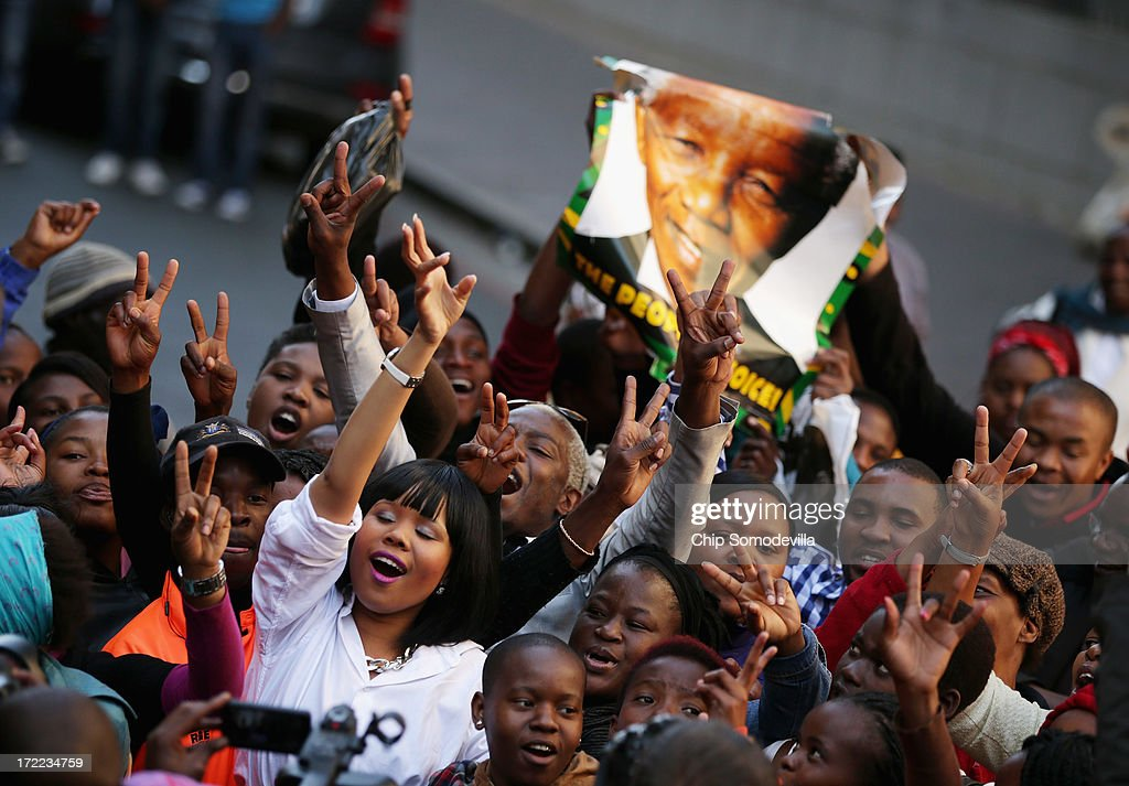People pray and sing songs of support for former South African President Nelson Mandela during an African National Congress-sponsored prayer rally outside ANC headquarters July 2, 2013 in Johannesburg, South Africa. The anti-apartheid icon and Nobel Peace Prize laureate has been in the hospital for more than three weeks being treated for a recurring lung infection.