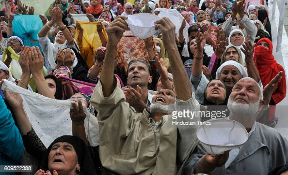 People pray as a head priest displays a holy relic believed to be the hair from the beard of the Prophet Muhammad at the Hazratbal Shrine on...