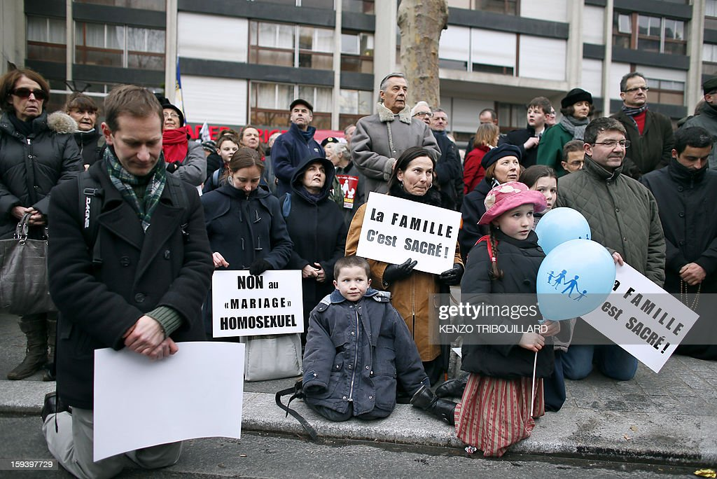 People pray as they hold placards reading 'Family is sacred !' and 'No to Homosexual +marriage+' during a protest organized by fundamentalist Christians group Civitas Institute against same-sex marriage on January 13, 2013 in Paris. Tens of thousands march in Paris on January 13 to denounce government plans to legalise same-sex marriage and adoption which have angered many Catholics and Muslims, France's two main faiths, as well as the right-wing opposition. The French parliament is to debate the bill -- one of the key electoral pledges of Socialist President -- at the end of this month.