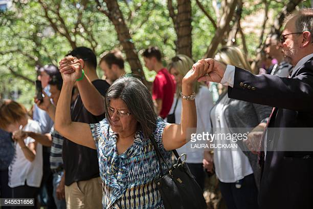 People pray at a faith vigil at ThanksGiving Square in Dallas Texas on July 8 following the shootings during a peaceful protest on July 7 which left...