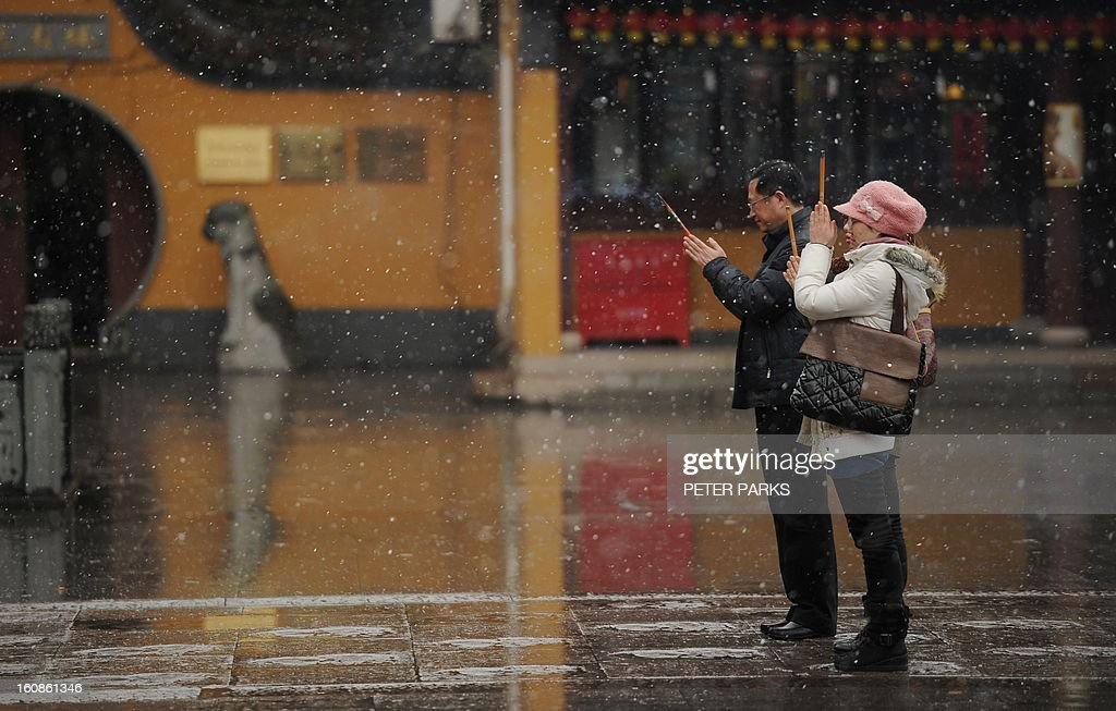 People pray at a temple as it snows in Shanghai on February 7, 2013 ahead of the Lunar New Year. Preparations continue for the Lunar New Year which will celebrate the start of the Year of the Snake on February 10. AFP PHOTO / Peter PARKS