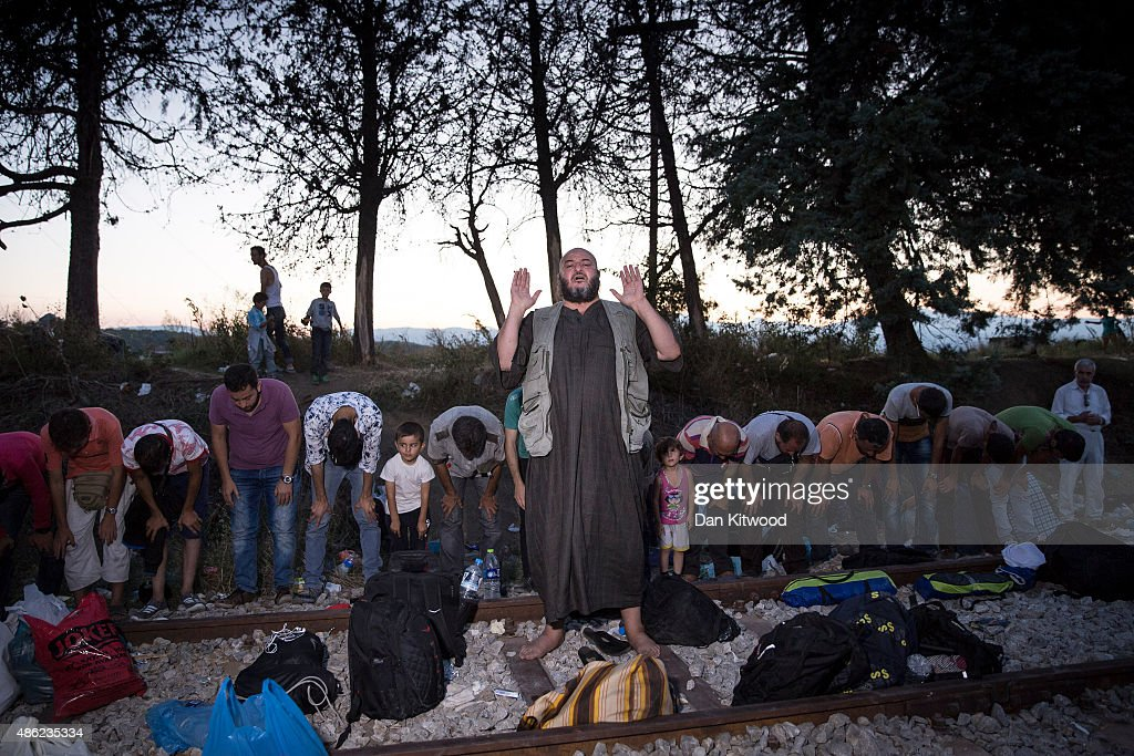 People pray at sunset as families wait along with hundreds of other on train tracks at the Greek Macedonian border on September 2, 2015 in Idomeni Greece. Several thousand migrant people are expected to arrive at the border today hoping to head North through Macedonia, after arriving in Athens in the previous few days. Since the beginning of 2015 the number of migrants using the so-called 'Balkans route' has exploded with migrants arriving in Greece from Turkey and then travelling on through Macedonia and Serbia before entering the EU via Hungary. The number of people leaving their homes in war torn countries such as Syria, marks the largest migration of people since World War II.