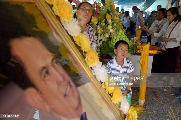 People pray at the grave of Cambodian critic Kem Ley during the first anniversary of his murder at his mother's home in Takeo province on July 9 2017...