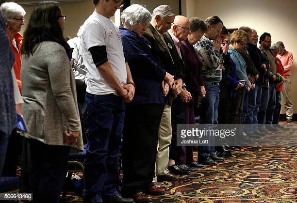 People pray before Republican presidential candidate Ben Carson spoke during his 'Trust in God' town hall event January 24 2016 in Marshalltown Iowa...