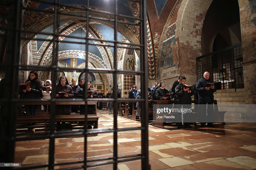 People pray during a mass at the Basilica of St. Francis of Assisi which holds the tomb of Saint Francis of Assisi on March 15, 2013 in Assisi, Italy. Cardinal Jorge Mario Bergoglio took the name Pope Francis after Saint Francis of Assisi who had renounced a life of privilege, by giving away all his possessions, wearing coarse woolen clothes and living in a humble hut after he took a vow of poverty.