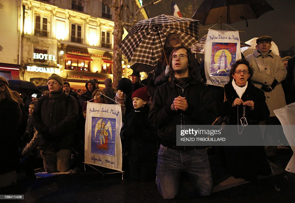 People pray during a protest organized by fundamentalist Christians group Civitas Institute against same-sex marriage on January 13, 2013 in Paris. Tens of thousands march in Paris on January 13 to denounce government plans to legalise same-sex marriage and adoption which have angered many Catholics and Muslims, France's two main faiths, as well as the right-wing opposition. The French parliament is to debate the bill -- one of the key electoral pledges of Socialist President -- at the end of this month. AFP PHOTO / KENZO TRIBOUILLARD