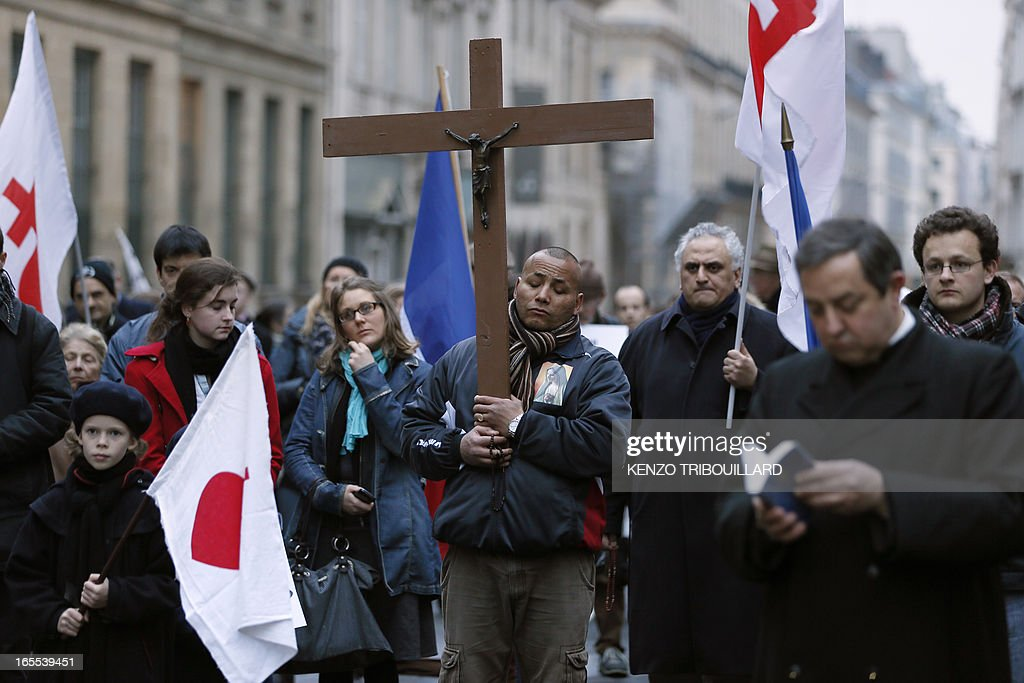People pray during a protest organized by fundamentalist Christians group Civitas Institute against same-sex marriage on April 4, 2013 in front of the French Senate in Paris on the first day of the debate at France's upper house on the controversial bill to legalise same-sex marriage and adoption. While the upper house is unlikely to reject the groundbreaking reform, it is still expected to be a tight vote as the ruling Socialists enjoy a smaller majority in the Senate than in the National Assembly. AFP PHOTO / KENZO TRIBOUILLARD