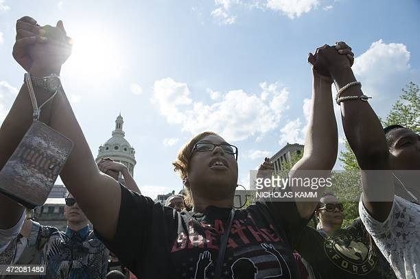 People pray during a rally in front of City Hall in Baltimore Maryland on May 3 2015 calling for peace following widespread riots The riots stemmed...