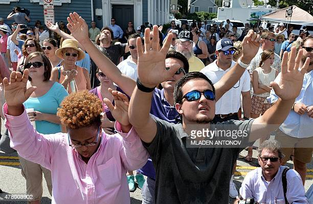 People pray during the Sunday service outside the Emanuel AME Church in Charleston South Carolina on June 21 2015 Large crowds arrived at Sunday's...