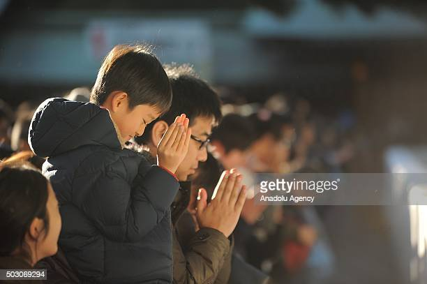 People pray for the New Year at the Meiji Shrine in Tokyo Japan on January 1 2016 Japanese go to Shrine to ask for health wealth and divine...