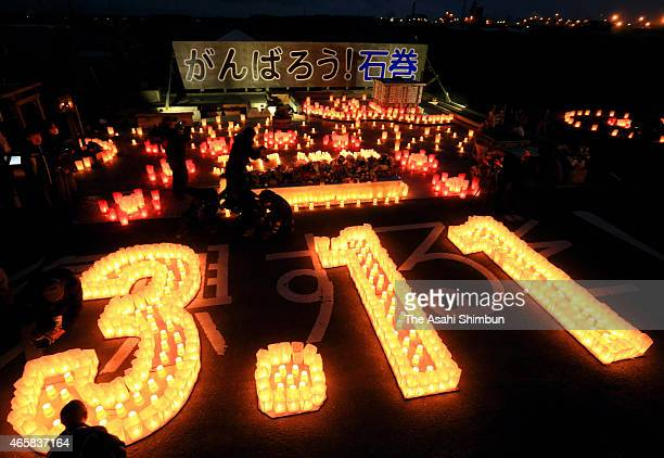People pray for the vectims at the numbers 311 lit by paper lanterns on the fourth anniversary of the Great East Japan Earthquake on March 11 2015 in...