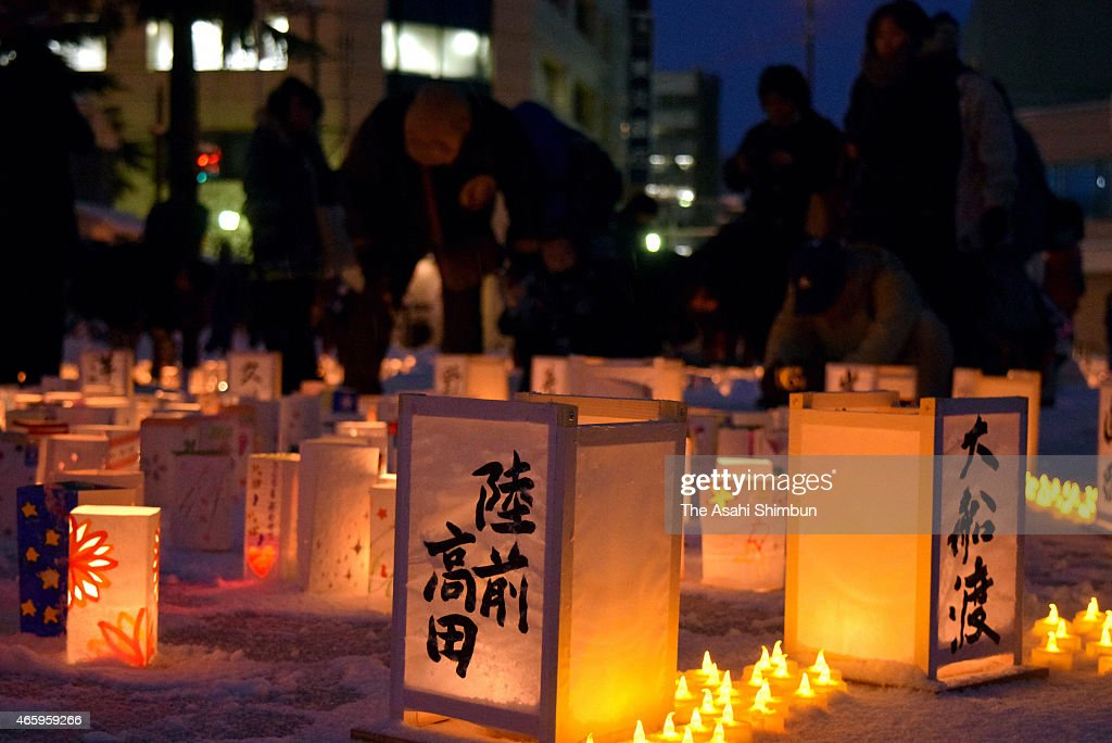 People pray for the vectims next to paper lanterns on the fourth anniversary of the Great East Japan Earthquake on March 11 2015 in Morioka Iwate...