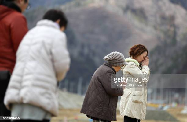 People pray for the victims at former Unosumai Disaster Prevention Center on the sixth anniversary of the Great East Japan Earthquake and following...