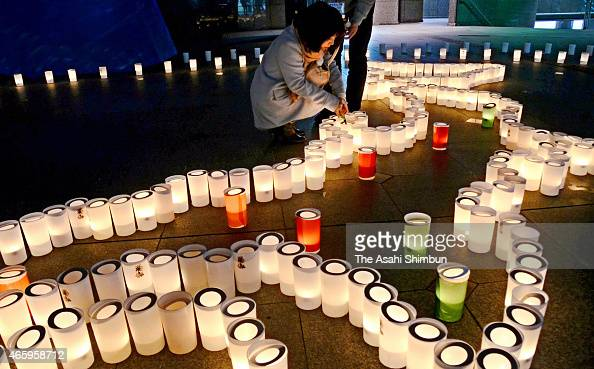People pray for the victims while Japanese map is formed with candles on the fourth anniversary of the Great East Japan Earthquake on March 11 2015...