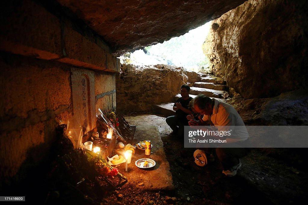 People pray for the war dead at 'Gama', the cave used as the evacuation place during the Battle of Okinawa, on June 23, 2013 in Itoman, Okinawa, Japan. During the 3-month ground battle at the end of World War II, more than 200,000 people were killed.