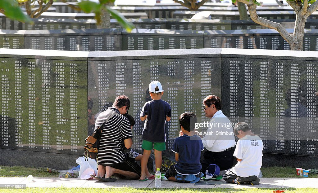 People pray for the war dead in front of Heiwa-no-Ishiji or 'Cornerstone of Peace', the memorial to commemorate Okinawa-related war victims, at Okinawa Prefecture Peace Memorial Parkon June 23, 2013 in Itoman, Okinawa, Japan. During the 3-month ground battle at the end of World War II, more than 200,000 people were killed.
