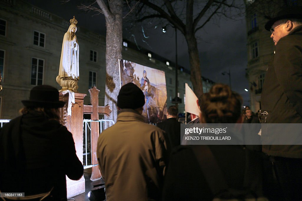 People pray in front of a statue of the virgin Mary during a protest organized by fundamentalist Christians group Civitas Institute against same-sex marriage on January 29, 2013 in Paris. France's parliament began today examining draft legislation on same-sex marriage after months of rancorous debate and huge street protests by both supporters and opponents.