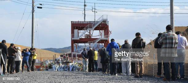People pray in front of former Minamisanriku City Disaster Prevention Center on the sixth anniversary of the Great East Japan Earthquake and...