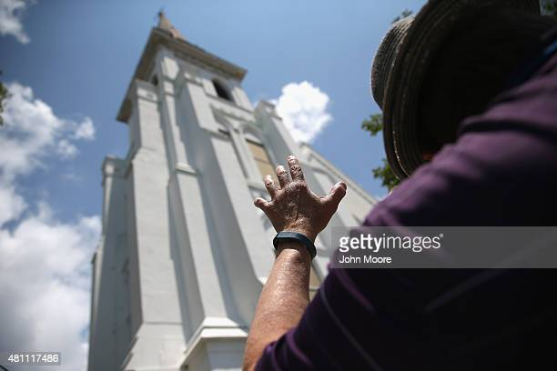 People pray in front of the Emanuel AME Church on the onemonth anniversary of the mass shooting on July 17 2015 in Charleston South Carolina Visitors...