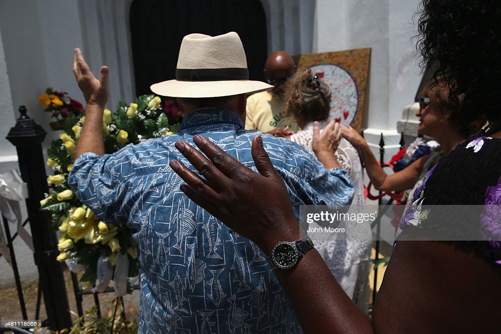 People pray in front of the Emanuel AME Church on the one-month anniversary of the mass shooting on July 17, 2015 in Charleston, South Carolina. Visitors from around the nation continue to pay their respects at a makeshift shrine in front of the church, in a show of faith and solidarity with 'Mother Emanuel', as the church is known in Charleston. Nine people were allegedly murdered on June 17 by 21-year-old white supremacist Dylann Roof, who was captured by police in North Carolina the following day. He is scheduled to go to trial July 11, 2016.