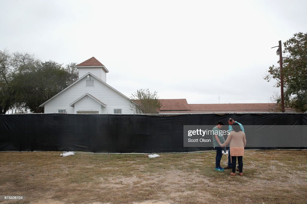 People pray in front of the First Baptist Church of Sutherland Springs on November 12, 2017 in Sutherland Springs, Texas. The congregation held service today in a tent on the towns ball park. Today the original church will open to visitors as a memorial to the victims who were shot during last Sunday's service. Residents of the community are still trying to heal following the shooting. Devin Patrick Kelley shot and killed the 26 people and wounded 20 others when he opened fire during Sunday service at the church.
