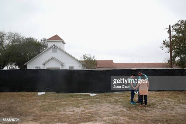 People pray in front of the First Baptist Church of Sutherland Springs on November 12 2017 in Sutherland Springs Texas The congregation held service...