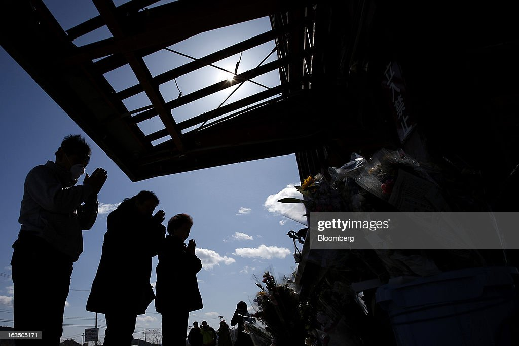 People pray in front of the remaining structure of a former disaster center to commemorate the second anniversary of the Great East Japan Earthquake and Tsunami in Minamisanriku, Miyagi Prefecture, Japan, on Monday, March 11, 2013. Two years after a record earthquake devastated Japan's northeast, Prime Minister Shinzo Abe has driven the nation's bond risk to levels from before the disaster with a plan that will add to the world's biggest debt burden. Photographer: Kiyoshi Ota/Bloomberg via Getty Images