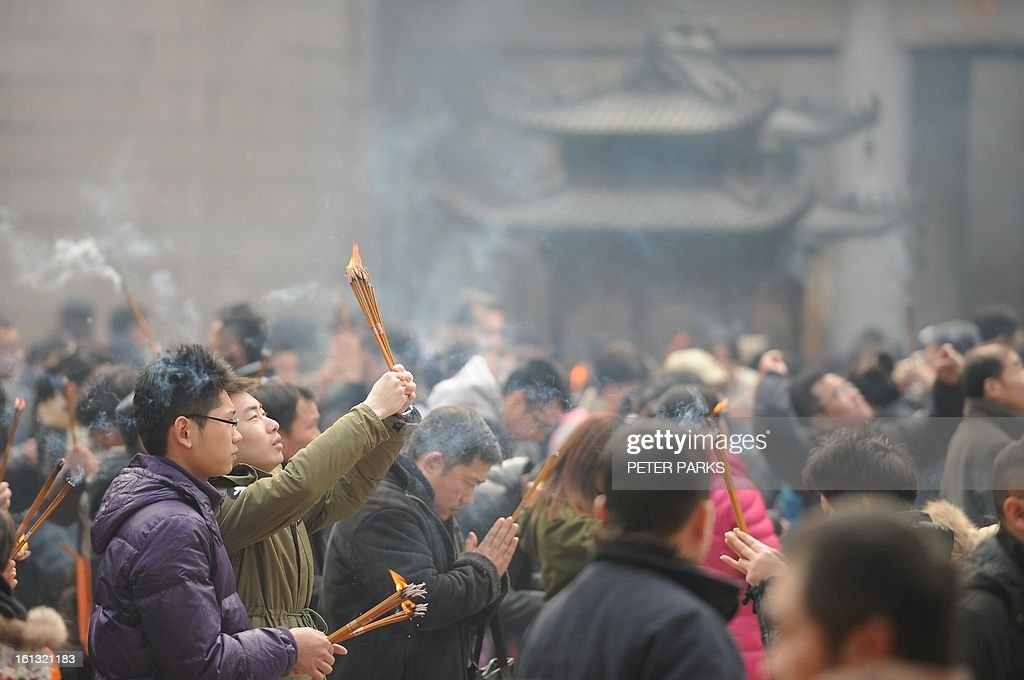 People pray in the Jing An temple in Shanghai as a billion-plus Asians ushered in the Year of the Snake on on February 10, 2013. From Australia to South Korea, millions of people travelled huge distances to reunite with their families for Lunar New Year -- the most important holiday of the year for many in Asia -- indulging in feasts and celebrations. AFP PHOTO/Peter PARKS