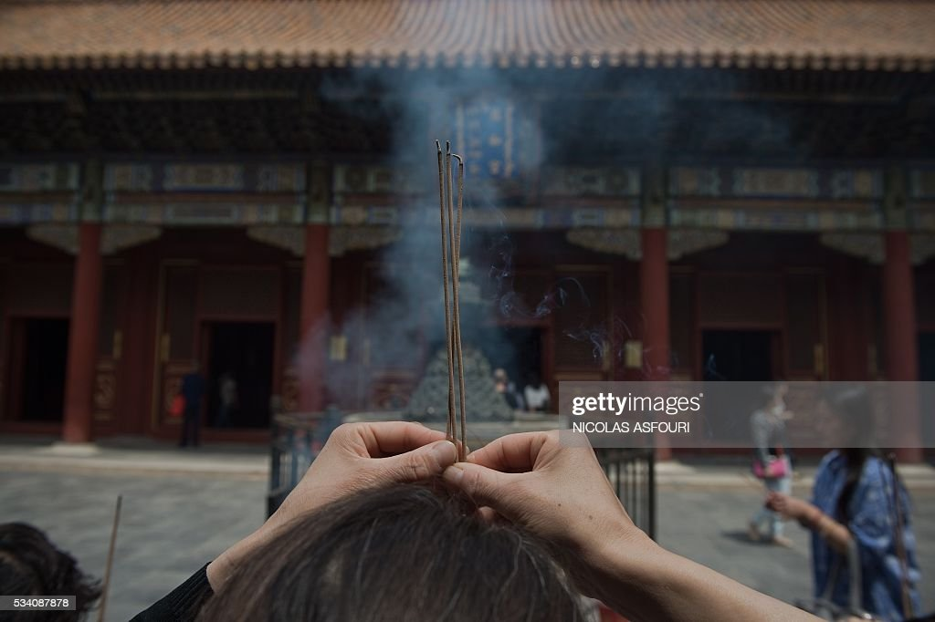 People pray inside the Lama temple in in Beijing on May 25, 2016. / AFP / NICOLAS