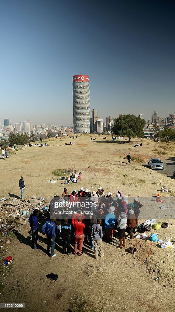 People pray on a hill overlooking downtown Johannesburg in the Yeoville neighbourhood on July 4, 2013 in Johannesburg, South Africa. The worn, arid space on top of the Yeoville hill offers worshipers of various Christian denominations from South African, Botswana, Zimbabwe, the Democratic Republic of Congo and other African nations an open-air space where they can publicly practice their faith with a scenic view of downtown Johannesburg.