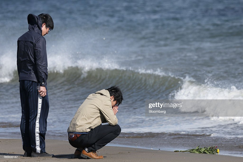 People pray on the second anniversary of the Great East Japan Earthquake and Tsunami at a coast damaged by the disaster in Sendai, Miyagi Prefecture, Japan, on Monday, March 11, 2013. Two years after a record earthquake devastated Japan's northeast, Prime Minister Shinzo Abe has driven the nation's bond risk to levels from before the disaster with a plan that will add to the world's biggest debt burden. Photographer: Kiyoshi Ota/Bloomberg via Getty Images