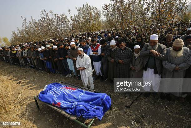 People pray over the body of Indian slain policeman Abdul Salam Khan at Kareva Shadab village in Shopian some 55 km of south of Srinagar on November...