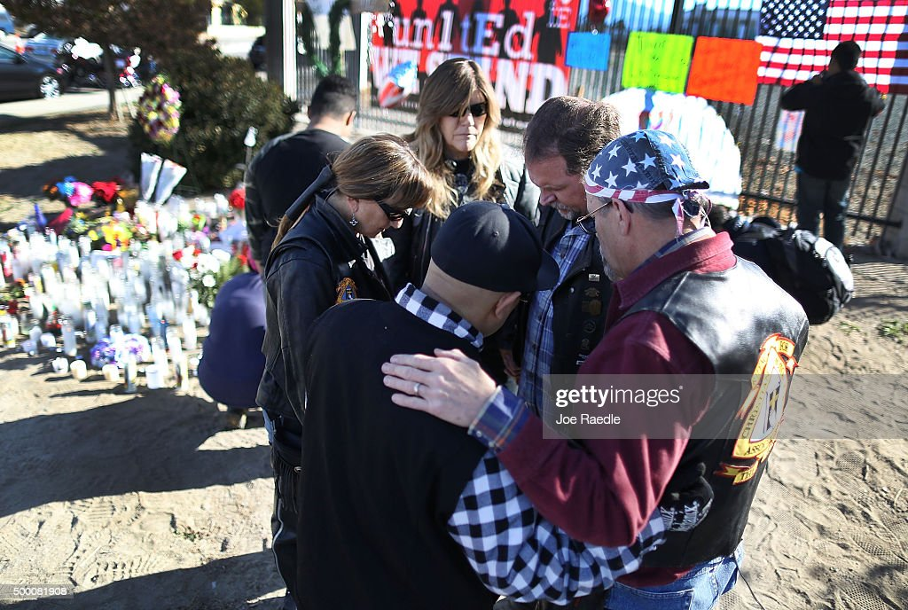 People pray together as they pay their respects at a memorial near the Inland Regional Center on December 5, 2015 in San Bernardino, California. Police continue to investigate a mass shooting at the Inland Regional Center in San Bernardino that left at least 14 people dead and another 17 injured on December 2nd.
