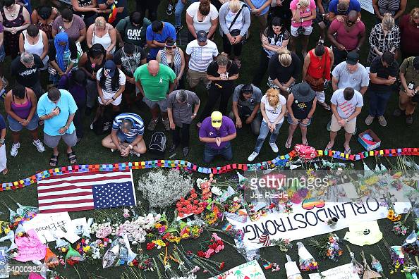 People pray together during a memorial service on the grounds in front of the Dr Phillips Center for the Performing Arts for the victims of the Pulse...