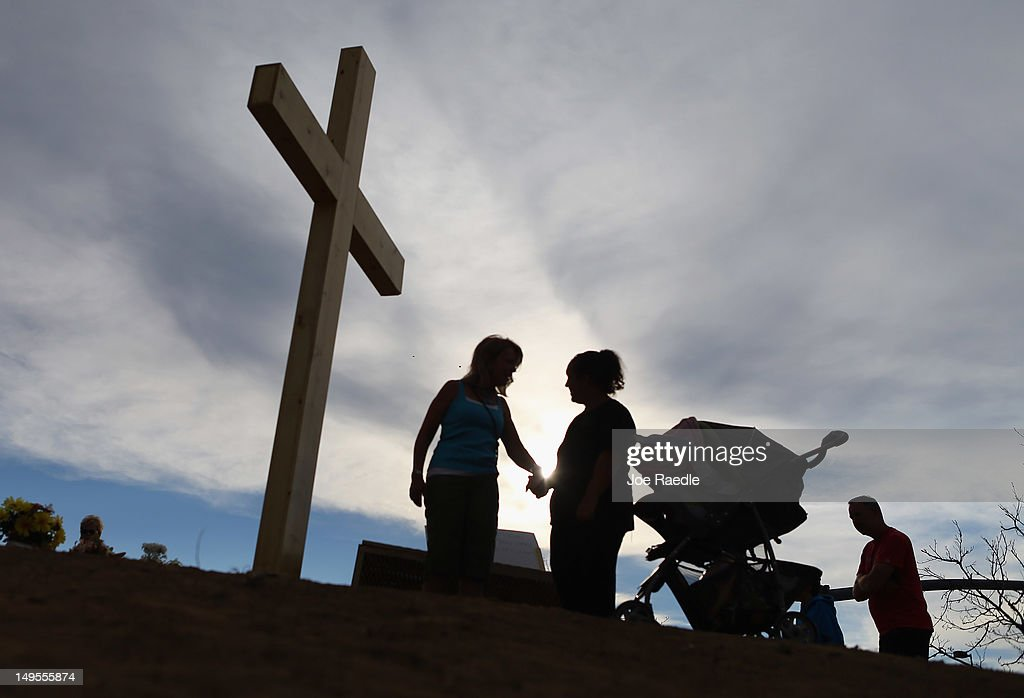 People pray together near a cross erected in a memorial setup across the street from the Century 16 movie theatre on July 30, 2012 in Aurora, Colorado. Twenty-four-year-old James Holmes is suspected of killing 12 and injuring 58 others during a shooting rampage at a screening of 'The Dark Knight Rises.'
