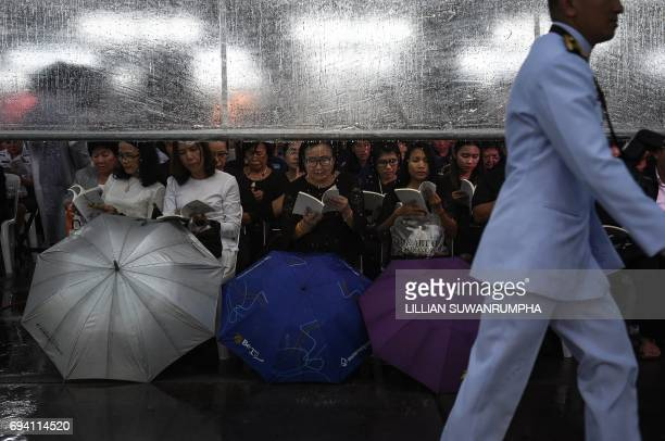 TOPSHOT People pray under a rain cover during a Buddhist ceremony for the late Thai King Bhumibol Adulyadej at the King Rama V Monument in Bangkok on...