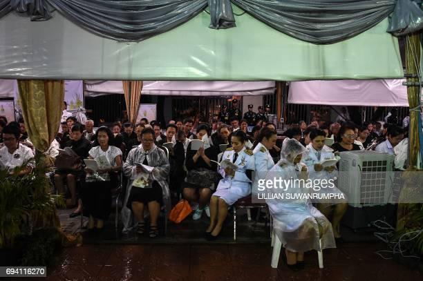 People pray under a rain cover during a Buddhist ceremony for the late Thai King Bhumibol Adulyadej at the King Rama V Monument in Bangkok on June 9...