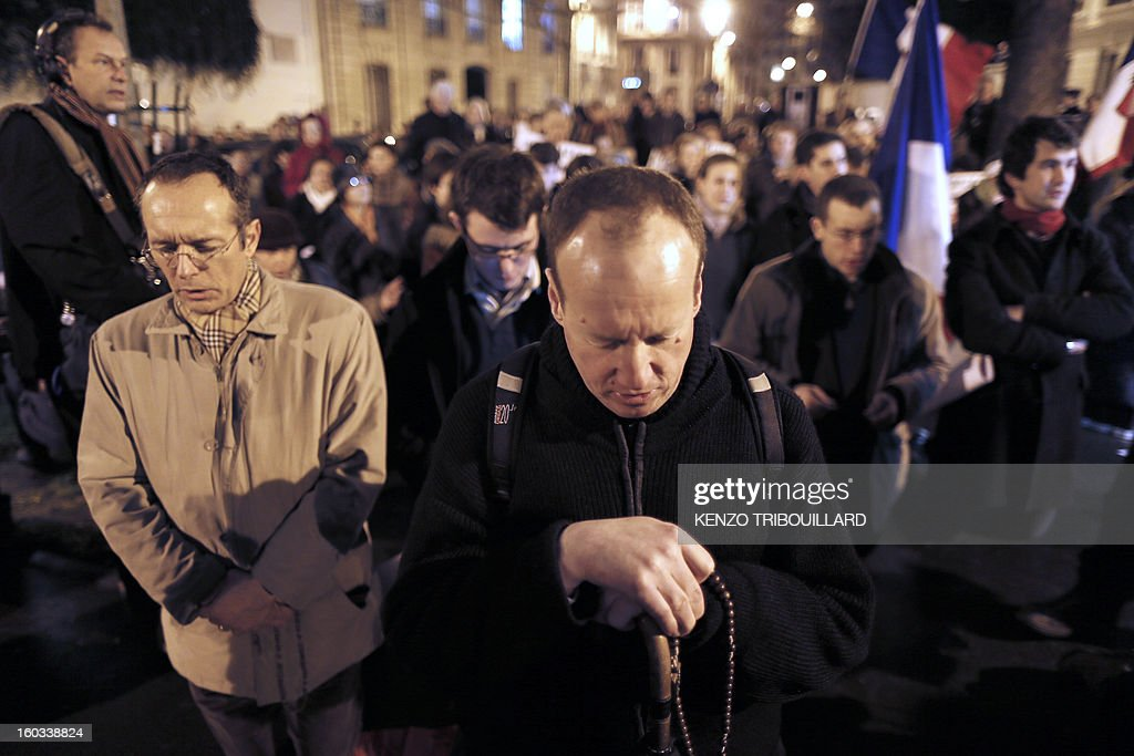 People pray with rosaries during a protest organized by fundamentalist Christians group Civitas Institute against same-sex marriage on January 29, 2013 in Paris. France's parliament began today examining draft legislation on same-sex marriage after months of rancorous debate and huge street protests by both supporters and opponents. Background, a French national flag with a sacred heart.