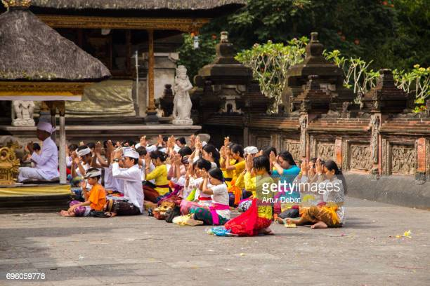 People praying in the Pura Tirta Empul, temple next to the holy spring waters of the temple where people go to purify.