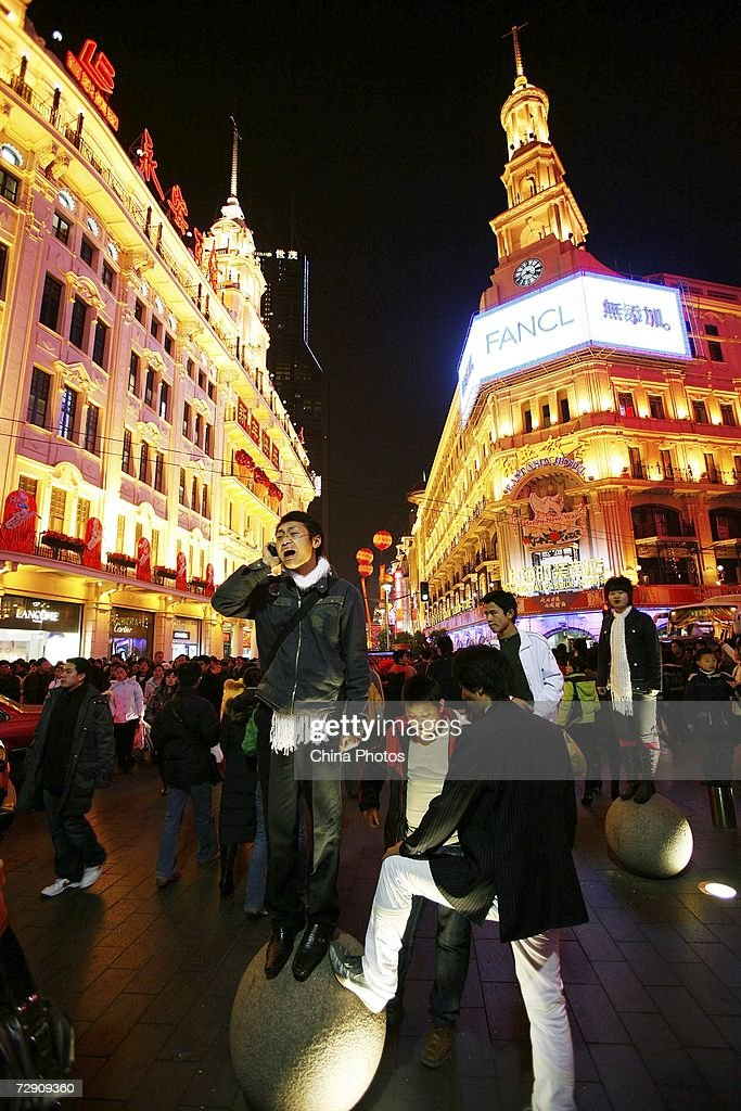 People prepare for New Year countdown at the Nanjing Road Shanghai's main shopping street on December 31 2006 in Shanghai China It is estimated that...