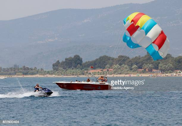 People prepare for parasailing on a boat in Izmir Turkey on July 25 2017 In Summer's extreme hot days people try to cool themselves off with various...