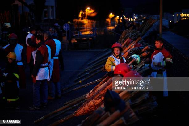 People prepare for the 'Chienbase' procession on March 5 2017 in Liestal northern Switzerland The procession takes place on the Sunday night after...
