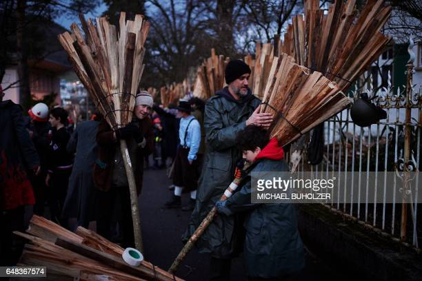 People prepare their bundles of pinewood chips before the 'Chienbase' procession on March 5 2017 in Liestal northern Switzerland The procession takes...
