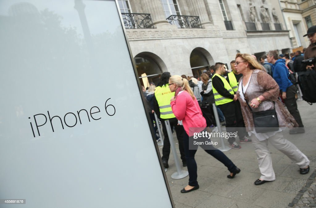 People prepare to enter the Apple Store on the first day of sales of the new Apple iPhone 6 in Germany on September 19 2014 in Berlin Germany...