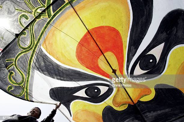 People prepare to fly a Peking Opera mask shaped kite at a square on March 31 2006 in Changchun of Jilin Province China Chinese people have...