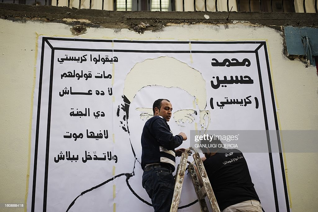 People prepare to paint the face of a protester who died during last week's demonstrations against Morsi and his Muslim Brotherhood on February 7, 2013 on a wall of Mohammed Mahmoud street prior to an anti-government demonstration in the city center of the Egyptian capital Cairo. The 23-year-old man, Mohammed Hussein Qarni died of a gunshot wound outside the presidential palace on February 1, where stone and petrol bomb throwing protesters faced off with police into the night. AFP PHOTO/GIANLUIGI GUERCIA