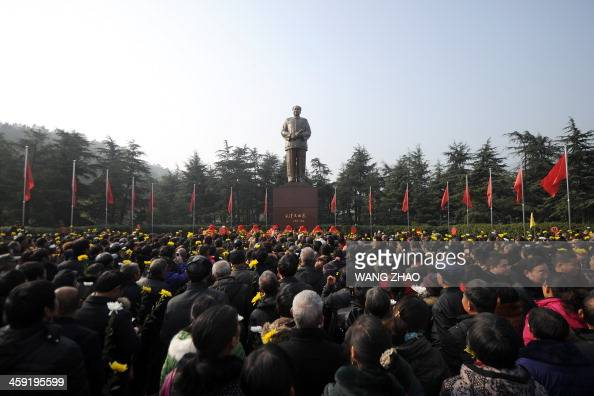 People prepare to present flowers to a bronze statue of China's former top leader Mao Zedong in Shaoshan in China's central province of Hunan on...