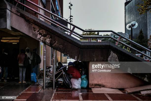 People prepare to sleep under stairs on November 13 2017 in a street of Lyon three days after having been expelled from a makeshift camp not far from...