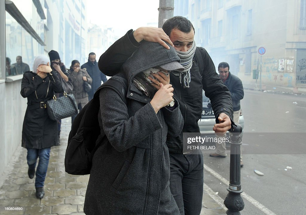 People protect themselves from tear gas smoke during clashes between Tunisian police and protesters following a rallye outside the Interior ministry to protest after Tunisian opposition leader and outspoken government critic Chokri Belaid was shot dead, on February 6, 2013 in Tunis. The protesters, who massed on Habib Bourguiba Avenue, epicentre of the 2011 uprising that ousted ex-dictator Zine El Abidine Ben Ali, pelted the police with bottles and the police responded by firing tear gas, chasing the protesters and beating them with batons. AFP PHOTO / FETHI BELAID